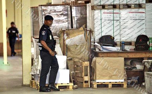 Police officers guard the Star Printery company premises during the printing of the ballot papers in Suva yesterday.